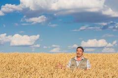 Agricoltore che sta in un giacimento di grano Fotografie Stock Libere da Diritti