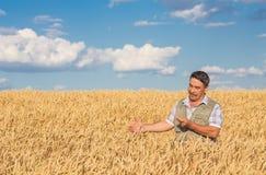 Agricoltore che sta in un giacimento di grano Fotografie Stock