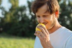 Agricoltore che tiene piccolo melone vicino al fronte e che esamina l'azienda agricola organica del melone della macchina fotogra Fotografie Stock Libere da Diritti