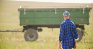 Agricoltore che utilizza compressa digitale mentre esaminando trattore nell'azienda agricola archivi video