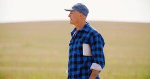 Agricoltore che utilizza compressa digitale mentre esaminando trattore nell'azienda agricola video d archivio