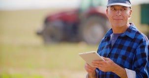 Agricoltore che utilizza compressa digitale mentre esaminando trattore nell'azienda agricola stock footage