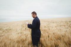 Agricoltore che utilizza compressa digitale nel campo Fotografie Stock Libere da Diritti