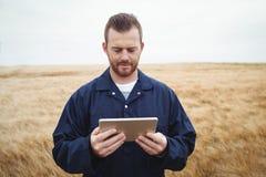 Agricoltore che utilizza compressa digitale nel campo Fotografia Stock Libera da Diritti