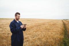 Agricoltore che utilizza compressa digitale nel campo Immagini Stock