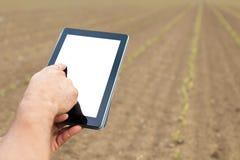 Agricoltore che utilizza il computer della compressa nel campo coltivato agricolo W Immagini Stock