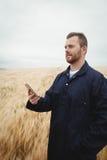 Agricoltore che utilizza telefono cellulare nel campo Immagine Stock