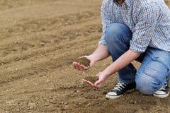 Agricoltore Checking Soil Quality della terra agricola fertile dell'azienda agricola Immagini Stock Libere da Diritti
