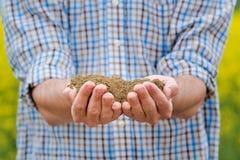 Agricoltore Checking Soil Quality della terra agricola fertile dell'azienda agricola Immagine Stock