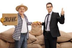 Agricoltore con dire del segno del cartone organico e dare dell'uomo d'affari Immagine Stock Libera da Diritti