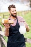Agricoltore con formaggio e latte Fotografia Stock Libera da Diritti