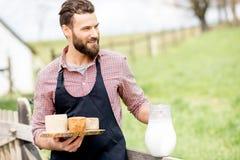 Agricoltore con formaggio e latte Fotografia Stock