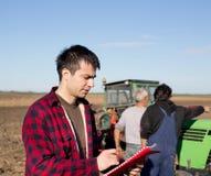Agricoltore con i lavoratori ed il trattore sul campo Fotografia Stock Libera da Diritti