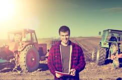 Agricoltore con i trattori nel campo Immagini Stock Libere da Diritti