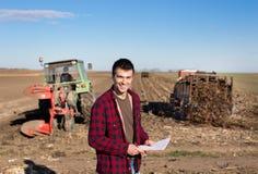Agricoltore con i trattori sul campo Immagini Stock