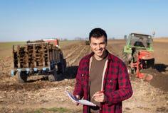 Agricoltore con i trattori sul campo Fotografie Stock