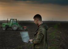 Agricoltore con il computer portatile davanti al trattore Immagini Stock