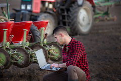 Agricoltore con il computer portatile ed i trattori Immagini Stock Libere da Diritti