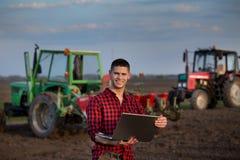 Agricoltore con il computer portatile ed i trattori Immagini Stock