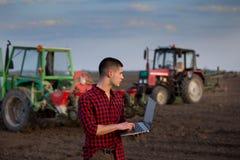 Agricoltore con il computer portatile ed i trattori Fotografie Stock Libere da Diritti