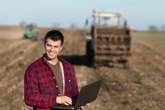 Agricoltore con il computer portatile ed i trattori sul campo Immagini Stock