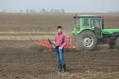 Agricoltore con il computer portatile ed il trattore Fotografia Stock