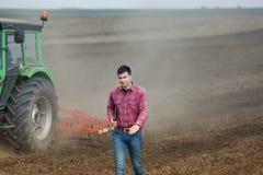 Agricoltore con il computer portatile ed il trattore Immagine Stock
