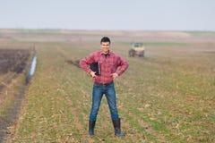Agricoltore con il computer portatile ed il trattore Immagine Stock Libera da Diritti