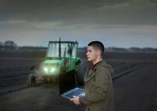 Agricoltore con il computer portatile ed il trattore Fotografia Stock Libera da Diritti