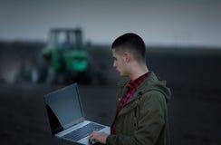 Agricoltore con il computer portatile ed il trattore Immagini Stock Libere da Diritti