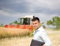 Agricoltore con il computer portatile nel campo Fotografie Stock