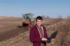 Agricoltore con il computer portatile nel campo Immagine Stock