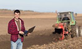 Agricoltore con il computer portatile nel campo Fotografia Stock