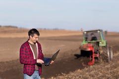 Agricoltore con il computer portatile nel campo Fotografia Stock Libera da Diritti