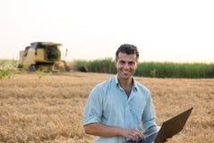 Agricoltore con il computer portatile nel campo durante il raccolto Fotografia Stock Libera da Diritti