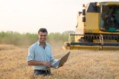 Agricoltore con il computer portatile nel campo durante il raccolto Immagine Stock Libera da Diritti