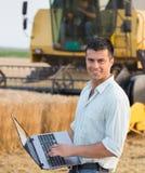 Agricoltore con il computer portatile nel campo durante il raccolto Immagini Stock Libere da Diritti