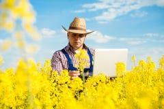 Agricoltore con il computer portatile nel giacimento di fioritura del seme di ravizzone Immagine Stock