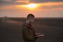 Agricoltore con il computer portatile sul campo Fotografia Stock