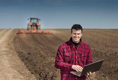 Agricoltore con il computer portatile sul terreno coltivabile Fotografia Stock Libera da Diritti
