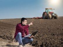 Agricoltore con il computer portatile sul terreno coltivabile Immagini Stock