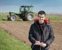 Agricoltore con il computer portatile sul terreno coltivabile Fotografie Stock