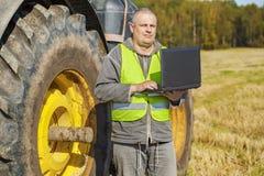 Agricoltore con il computer vicino al trattore sul campo Immagini Stock