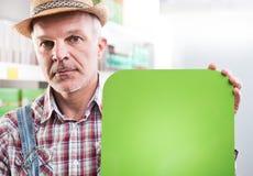 Agricoltore con il segno al supermercato Fotografia Stock