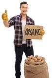 Agricoltore con il segno del cartone della tenuta del sacco della tela da imballaggio ed il pollice dare Immagine Stock Libera da Diritti