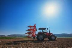 Agricoltore con il trattore che semina i raccolti al campo Immagini Stock