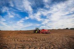 Agricoltore con il trattore che semina i raccolti al campo Fotografie Stock Libere da Diritti
