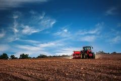 Agricoltore con il trattore che semina i raccolti al campo Fotografia Stock