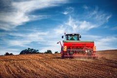 Agricoltore con il trattore che semina i raccolti al campo Immagini Stock Libere da Diritti