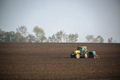 Agricoltore con il trattore che semina i raccolti al campo Immagine Stock Libera da Diritti